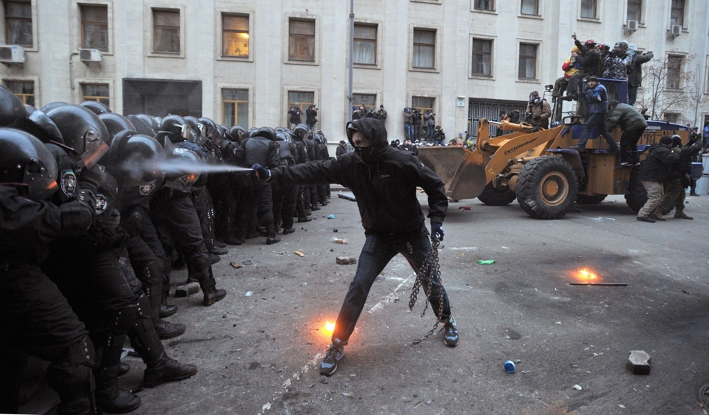 """afp. nagyításhoz - ne használd - 2013.12.A protester uses tear gas against riot police during the storming of the Viktor Yanukovych Presidential office in Kiev during a mass rally of the opposition on December 1, 2013. The crowd chanted """"Revolution!"""" and"""