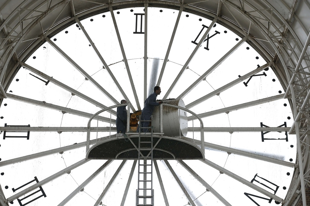 afp. óra, 2015.03.26. óraátállítás, Franciaország, Cergy, An employee climbs a ladder to check a huge clock, on March 26, 2015 in Cergy. France will change to daylight saving time on March 29, with the clocks moving forwards one hour.