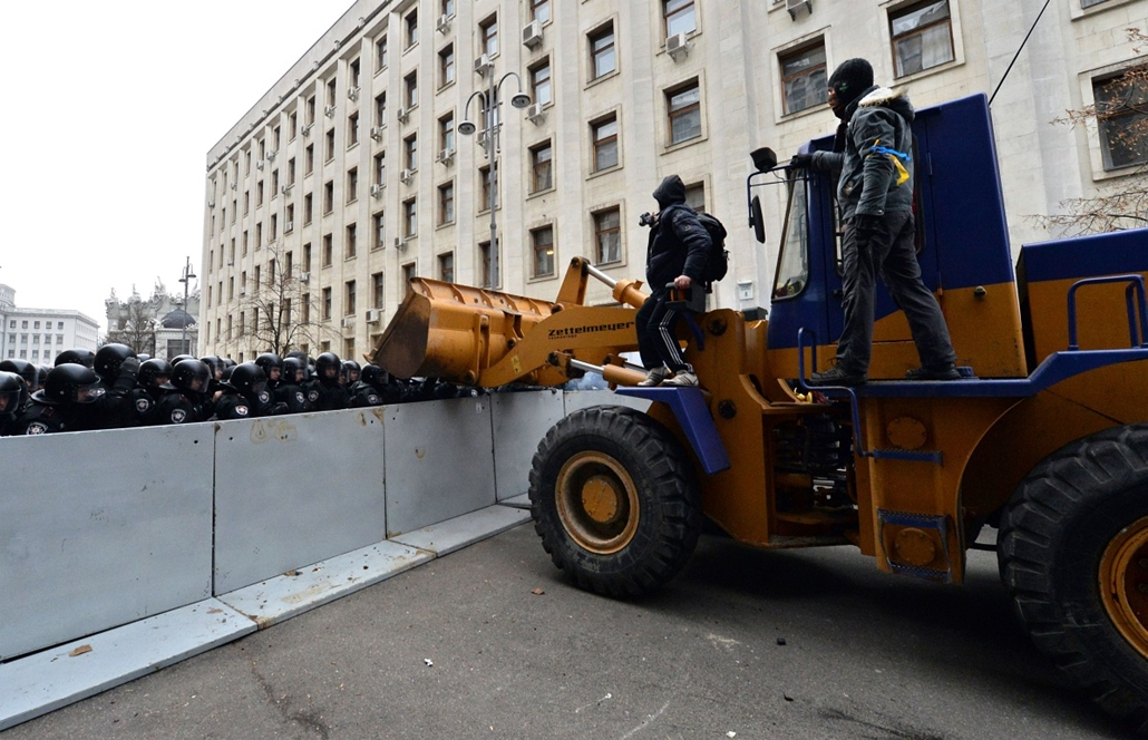 afp. nagyításhoz - ne használd - 2013.11.29. Pro-European Ukrainian demonstrators steer a bulldozer in front of police barricades protecting the presidential adminstration office in Kiev as 100 000 outraged Ukrainians swarmed the city in a call for early