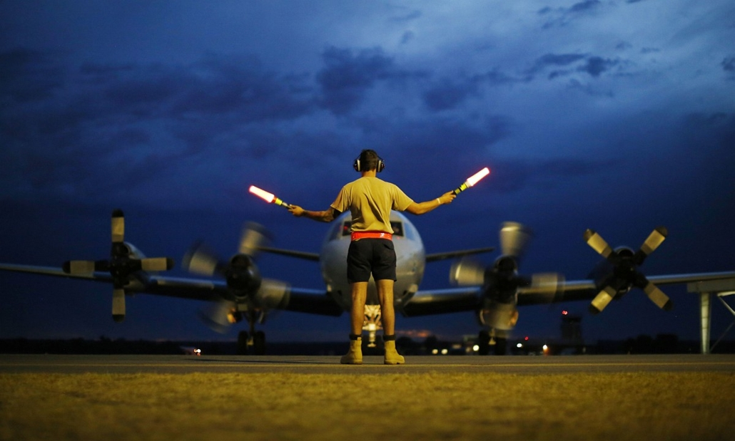 7 képei 0324-330 - Ausztrália, Bullsbrook, repülő, forgalom irányító - A ground controller guides a Royal Australian Air Force AP-3C Orion to rest after sunset upon its return from a search operation for the missing Malaysia Airlines flight MH370 over the