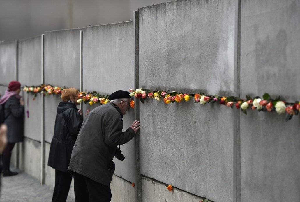 afp. Berlini fal leomlásA 25 éve 2014.11.09. Visitors look through a preserved segment of the Berlin Wall decorated with roses during the commemorations to mark the 25th anniversary of the fall of the Berlin Wall at the Berlin Wall Memorial in the Bernaue
