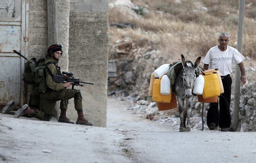 afp. hét képe 0623-0628 - Awarta 2014.06.26. Egy palesztin férfi vezet, a vizet hordó szamár - A Palestinian man leads a donkey carrying water jerrycans as Israeli soldiers take position during an army search operation in the West Bank village of Awarta o