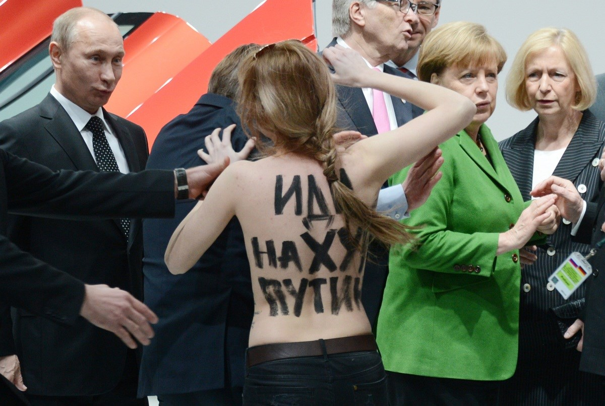 Fotók: félmeztelen aktivisták zavarták meg Merkelt és Putyint