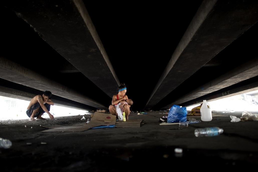 afp. nagyítás - hét képei - 2014.05.29. hajléktalan család Manila, Fülöp-szigetek - Homeless Richard Alcantara (L), 24, rests near his wife Joana, 18, holding their daughter, under a flyover in Manila on May 29, 2014. The Philippines' roaring economy cool