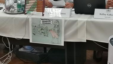 Egy Baranyi Krisztinát ábrázoló gúnyrajz lóg elődje, Bácskai János asztalán a közgyűlésen